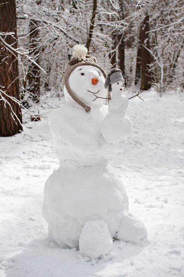 Pupazzo di neve con il pupazzo di neve del bambino fotografia stock libera da diritti