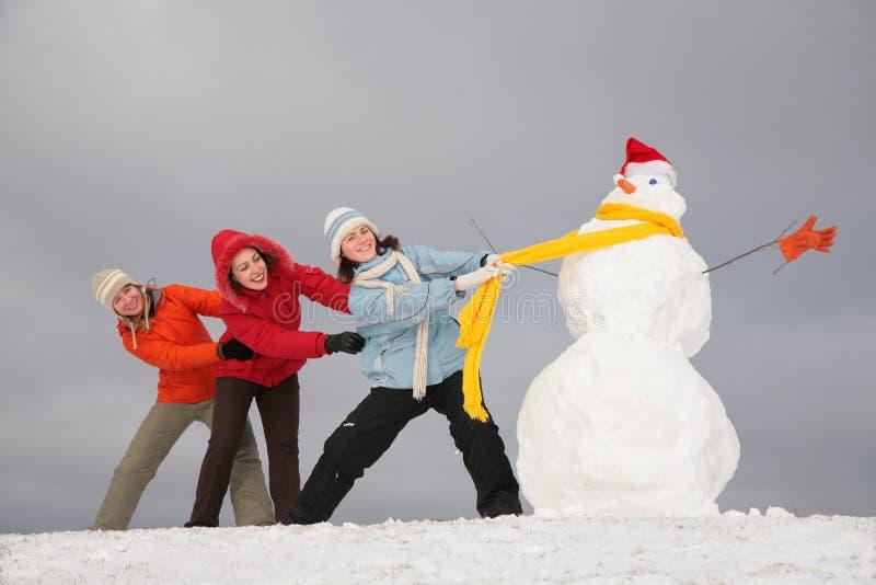 Pupazzo di neve di tiro delle tre ragazze dalla sciarpa fotografia stock