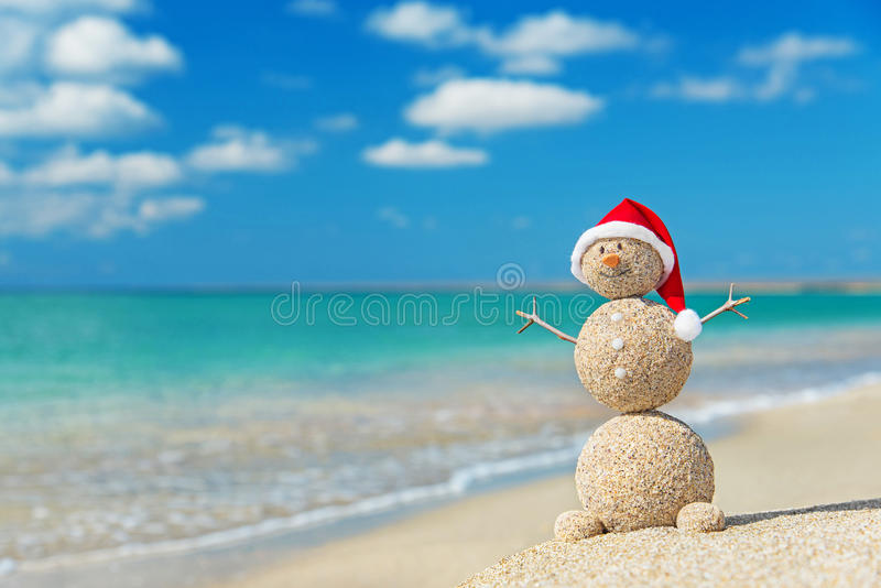 Pupazzo di neve sabbioso in cappello di Santa. Concetto di festa per i nuovi anni ed il Ch immagini stock libere da diritti
