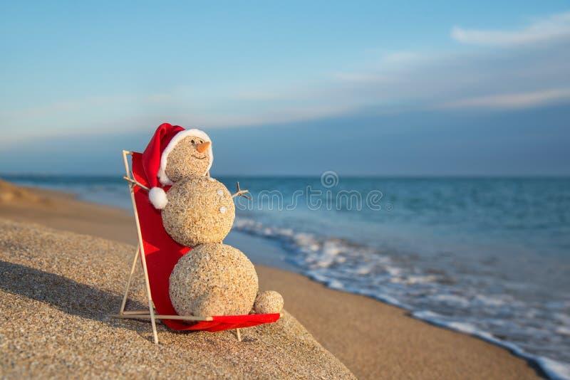 Pupazzo di neve sabbioso che prende il sole nel salotto della spiaggia. Concetto di festa per Ne immagini stock libere da diritti