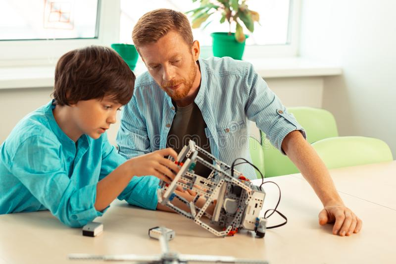 Pupil building a robot under supervision of his teacher. Giving advice. Hard-working student building a robot out of construction set under supervision of his royalty free stock photo