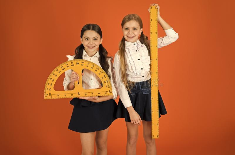 Pupil cute girls with big rulers. Geometry favorite subject. Education and school concept. School students learning royalty free stock images