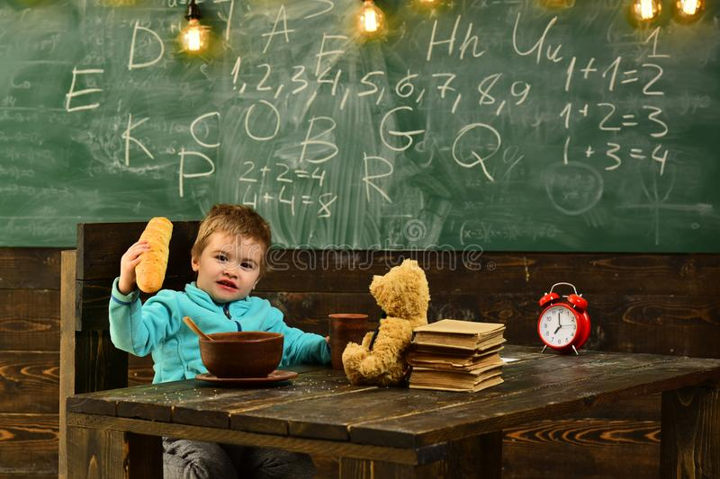 Pupil eat food at wooden table. Little pupil enjoy lunch break in classroom. School menu for pupil. Today is pupil royalty free stock photo