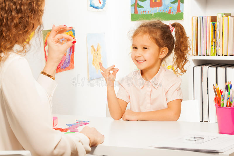 Pupil exercises putting fingers as her teacher royalty free stock photo