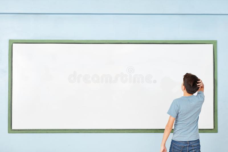 Pupil in front of whiteboard considering solution royalty free stock photography