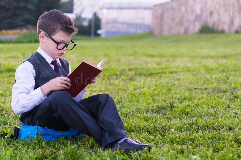 Pupil in glasses reads a book sitting on the grass royalty free stock image