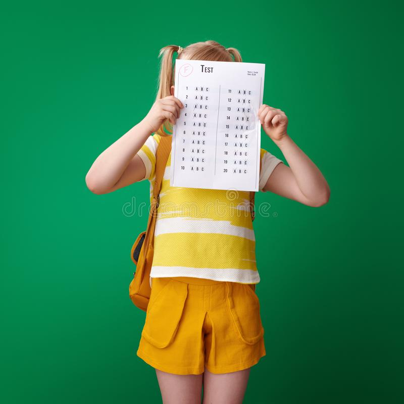 Pupil hiding behind bad grade test on green background. Pupil with backpack hiding behind a bad grade test on green background stock photos