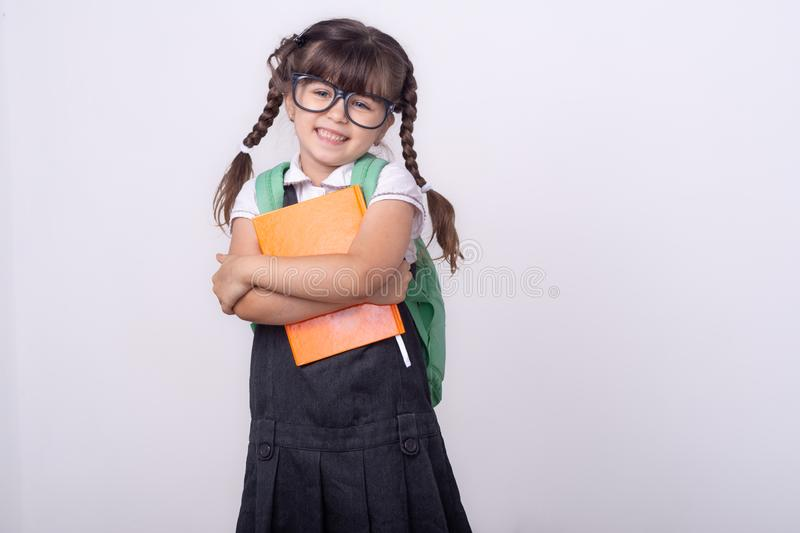 Pupil holding pen and notebook. Back to school. Little Student. Tidy hairstyle. stock photos