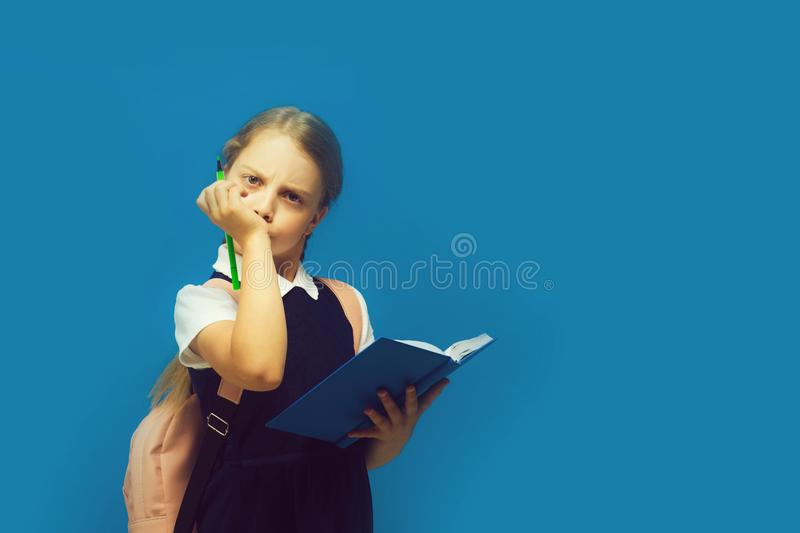 Pupil holds book and green marker. Back to school concept stock photography
