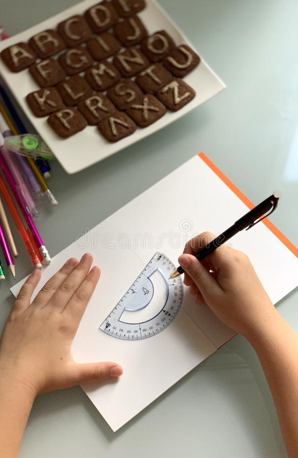 Pupil makes lessons. School subjects. Child's hands. stock image