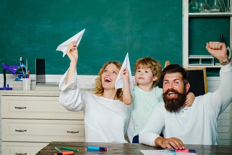 Pupil with paper airplane playing with parents. Young couple helping his son to make homework. Parent taking child to stock photos