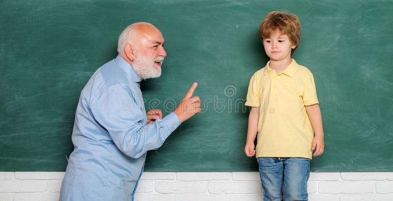 Pupil preparing for test or exam. Education and learning people concept - little student boy and Teacher using a laptop royalty free stock photo