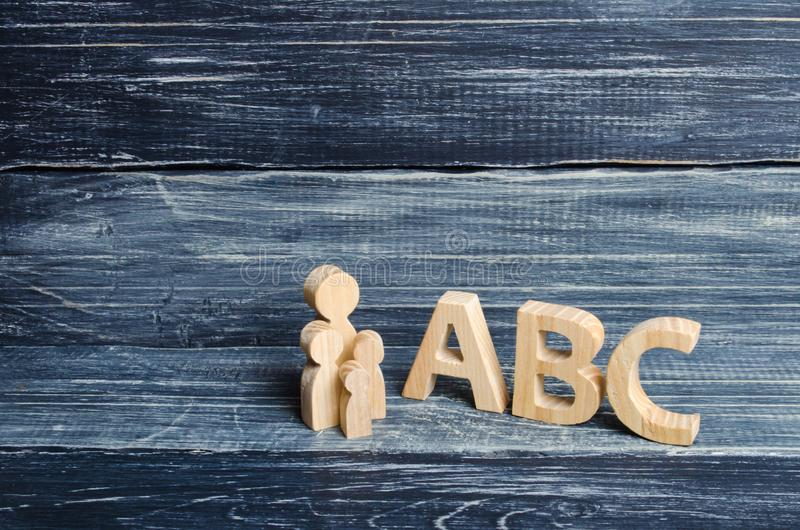 The pupil and pupils stand at the big letters ABC of the English alphabet. Parent and children. The concept of education. And upbringing of children royalty free stock photo