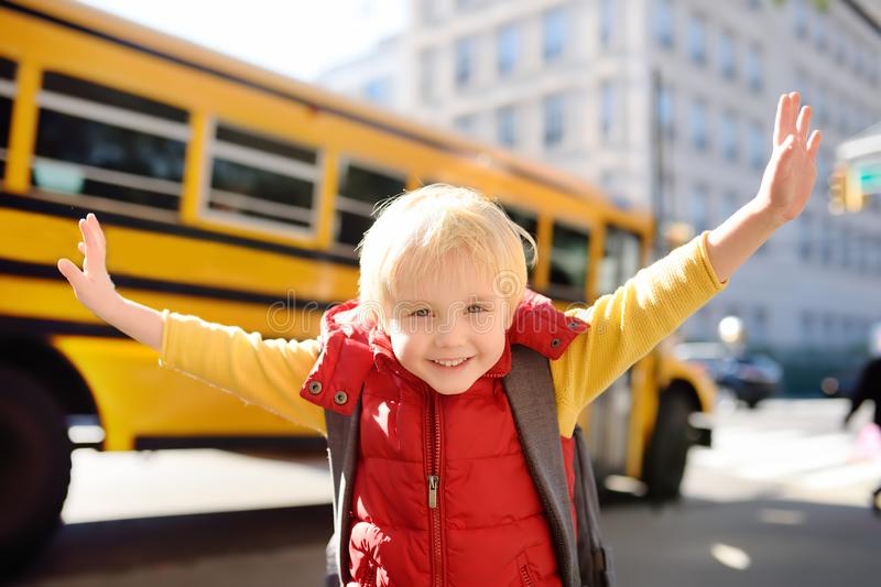Pupil with schoolbag with yellow school bus on background royalty free stock photo