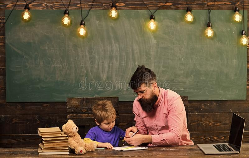 Pupil with teacher at school. Tutor helping kid to write letters in copybook. Man and boy sit at desk with laptop and royalty free stock images