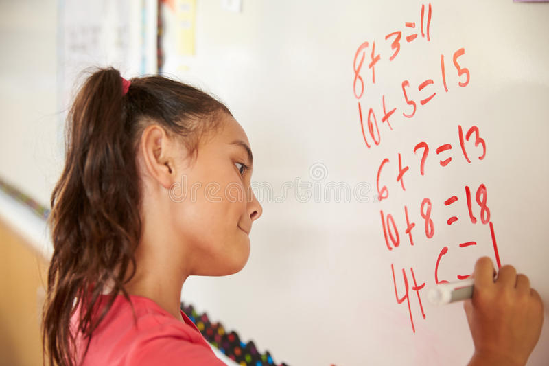 Pupil writing on the board at elementary school maths class stock images