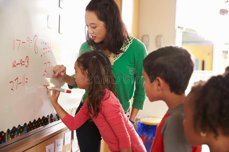 Pupil writing on the board at elementary school maths class royalty free stock images