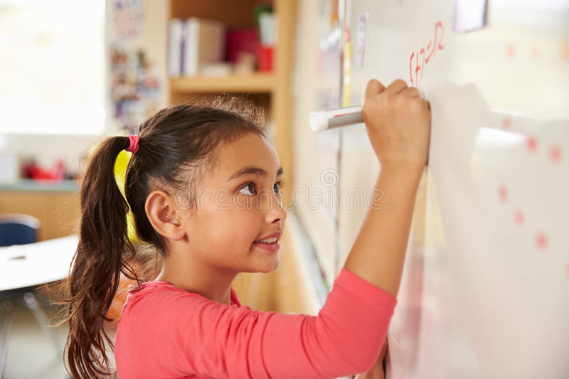 Pupil writing on the board at elementary school maths class stock photos