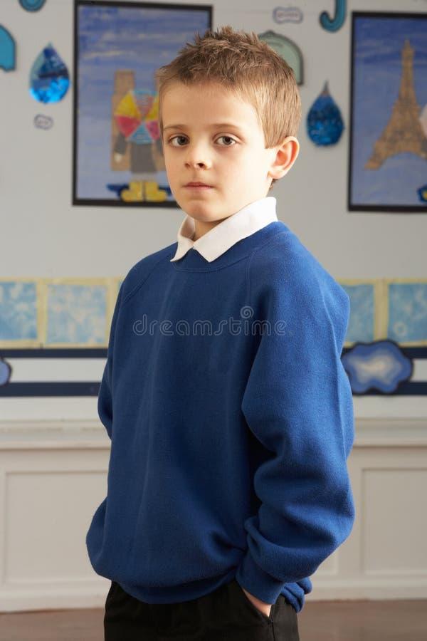 Pupila masculina de la escuela primaria que se coloca en sala de clase imágenes de archivo libres de regalías