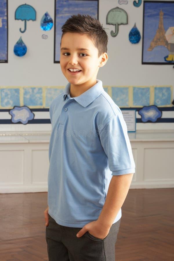 Pupila masculina de la escuela primaria que se coloca en sala de clase fotos de archivo