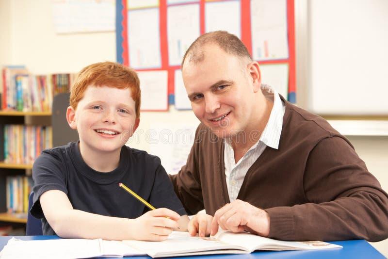 Pupila masculina que estudia en sala de clase con el profesor fotos de archivo libres de regalías