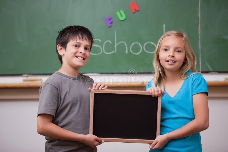 Pupilas sonrientes que sostienen una pizarra de la escuela imagenes de archivo
