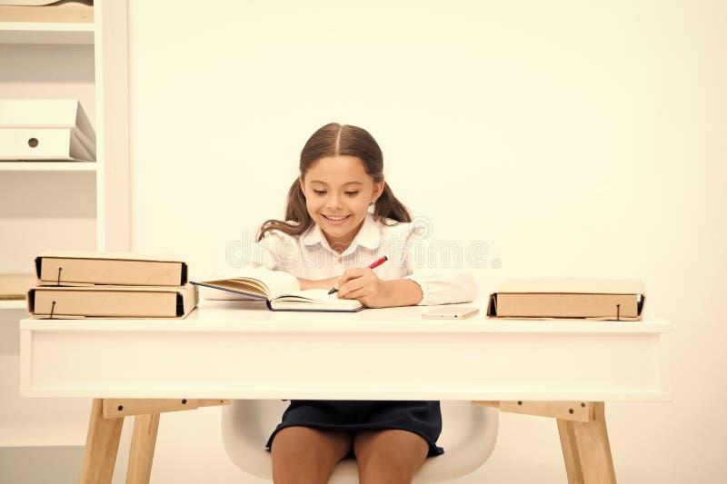 Pupilla eccellente Il bambino della ragazza scrive il hometask mentre sieda il fondo di bianco della tavola Scolara che studia sa fotografia stock