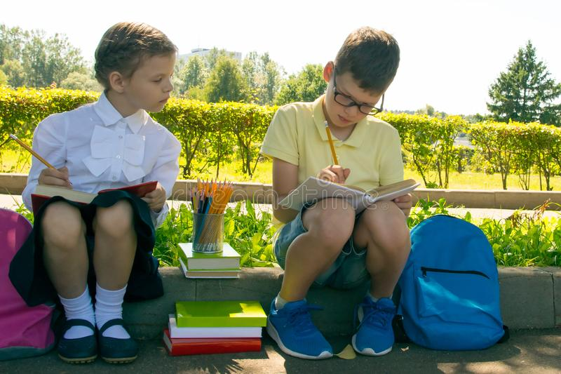 Pupils, a boy and a girl, doing tests of the school program, in the park outdoors, holding pencils royalty free stock photography