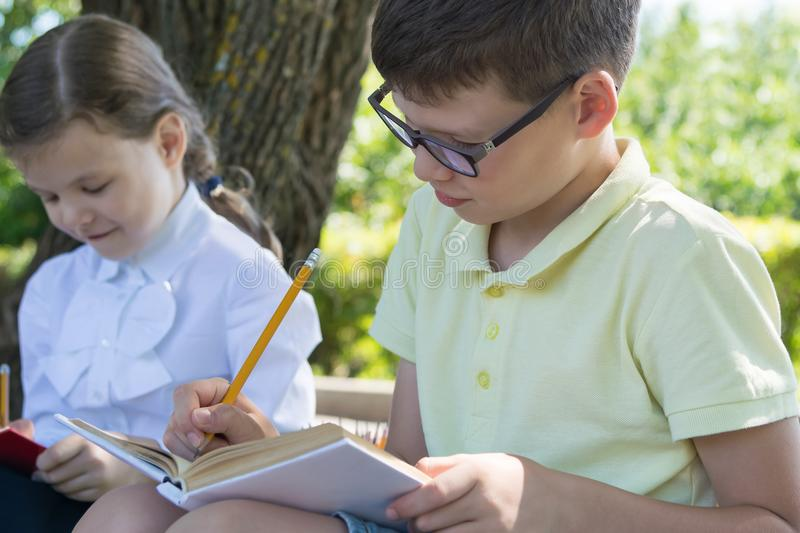 Pupils boy and girl are engaged in an outdoor lesson stock photo
