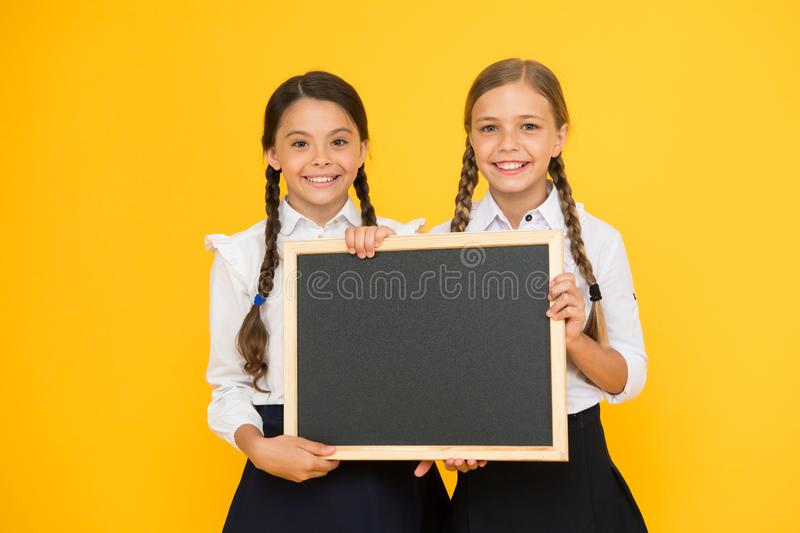 Pupils community. School schedule. School announcement concept. Check this out. School girls cute pupils hold blackboard stock photography