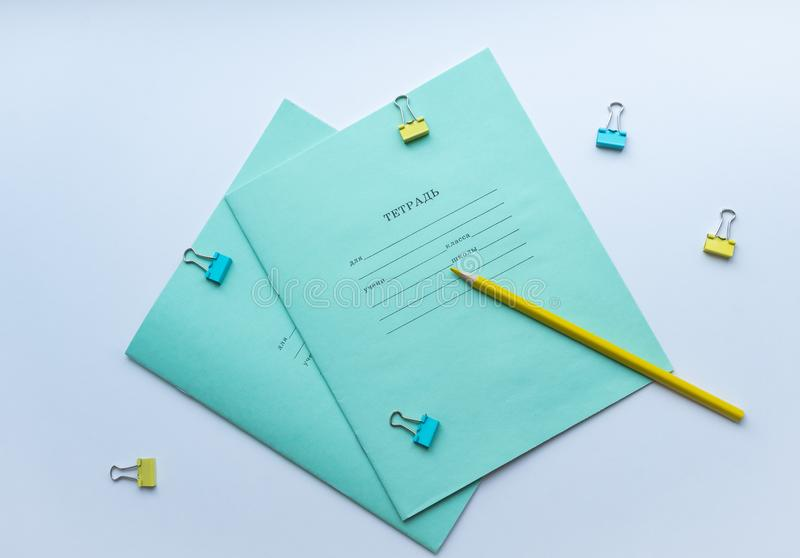 Top view of two pupils copybooks with form to sign in: name, surname, grade, etc. with yellow pencil and paper clips on white back. Ground. Concept of education royalty free stock photography