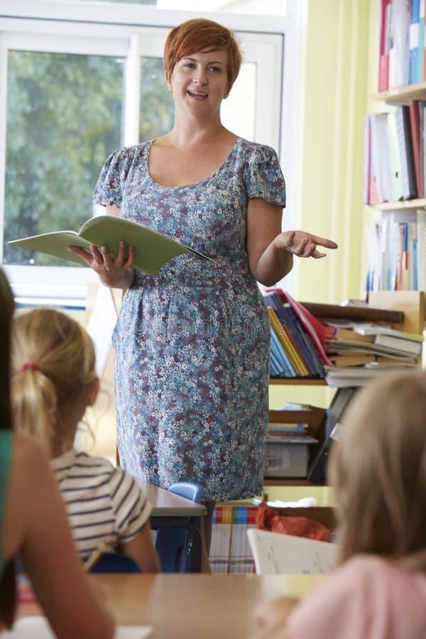 With Pupils In för grundskolalärare klassrum royaltyfria foton