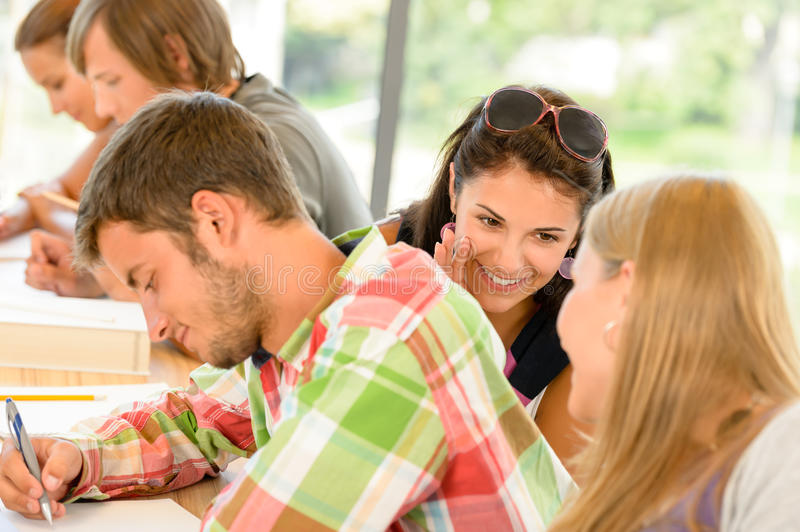 Pupils gossiping behind colleague's back in school. Class college teens stock image