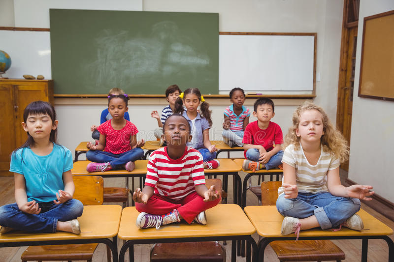 Pupils meditating in lotus position on desk in classroom. At the elementary school stock photos
