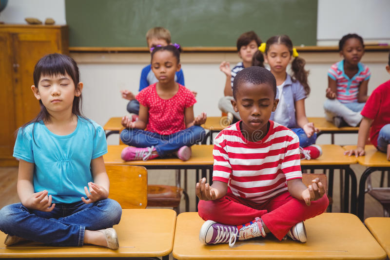 Pupils meditating in lotus position on desk in classroom. At the elementary school royalty free stock images