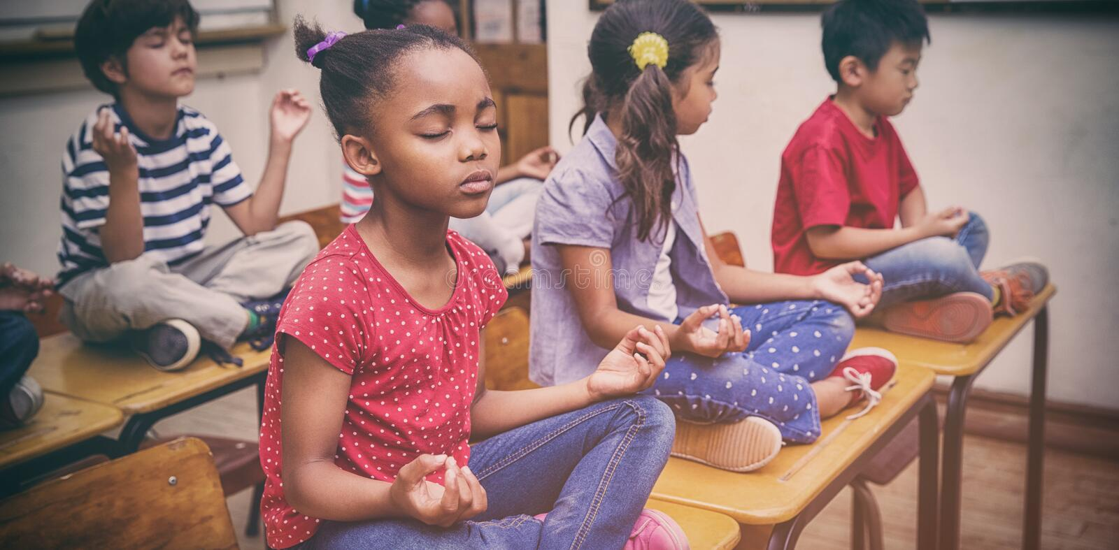Pupils meditating in lotus position on desk in classroom royalty free stock photography