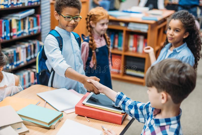 Pupils shaking hands. In school library stock photos