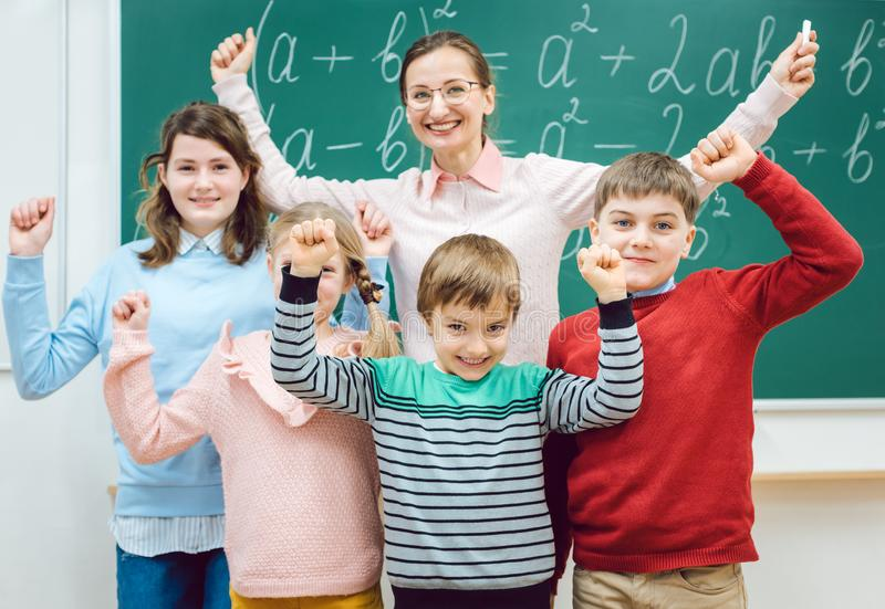 Pupils and teacher in class room having fun at school. Excited pupils and teacher in class room having fun at school stock image