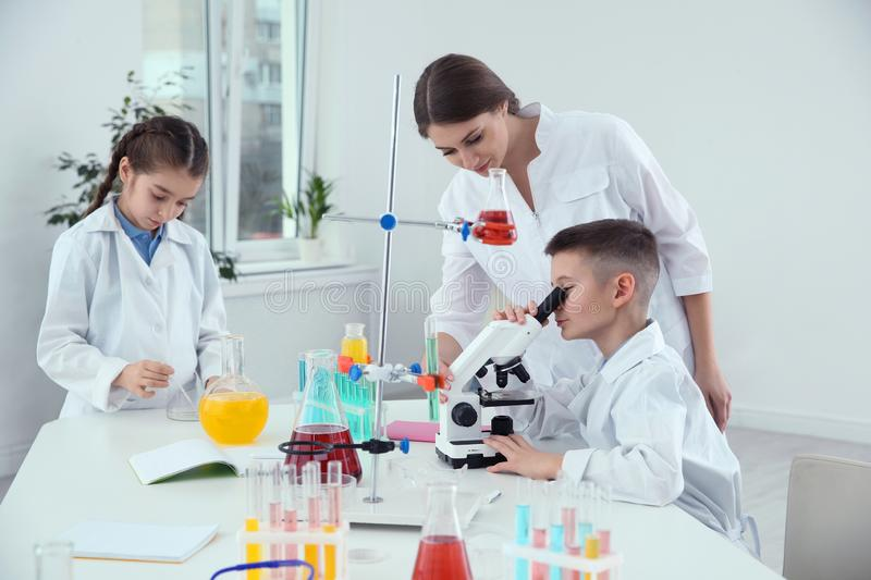 Pupils with their teacher at chemistry lesson royalty free stock photo