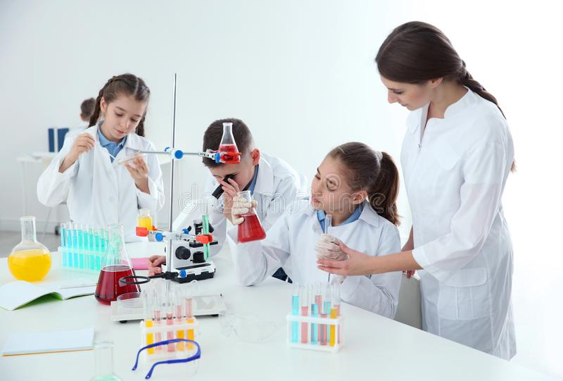 Pupils with their teacher at chemistry lesson stock photography