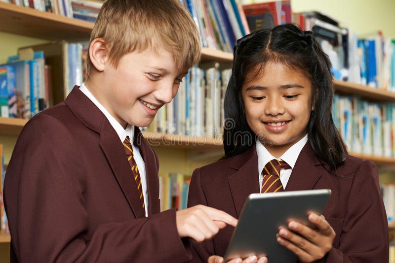 Pupils Wearing School Uniform Using Digital Tablet In Library. Pupils Wearing School Uniform Using Digital Tablet royalty free stock photography