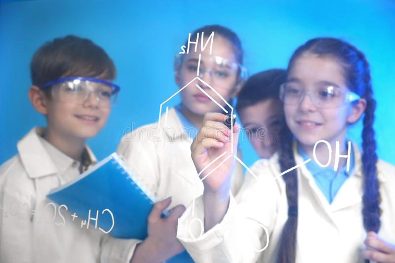 Pupils writing chemistry formula on glass board. Against color background royalty free stock photography
