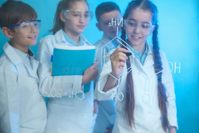Pupils writing chemistry formula on glass board. Against color background stock image