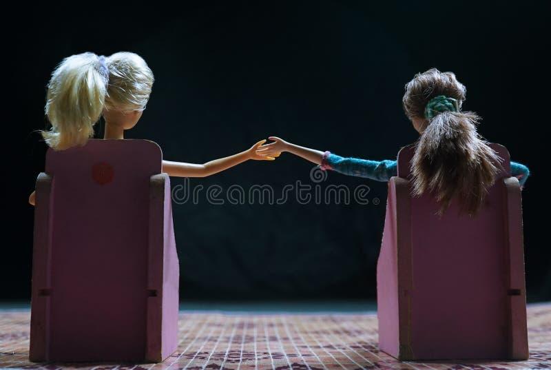 Puppen, die auf der Rückseite genommen von der Hand sitzen lizenzfreie stockbilder