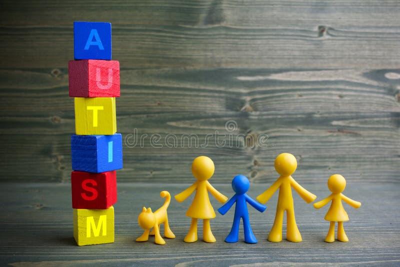 Puppenkinder entwerfen mit Autismuswort auf hölzernem Hintergrund stockfotografie