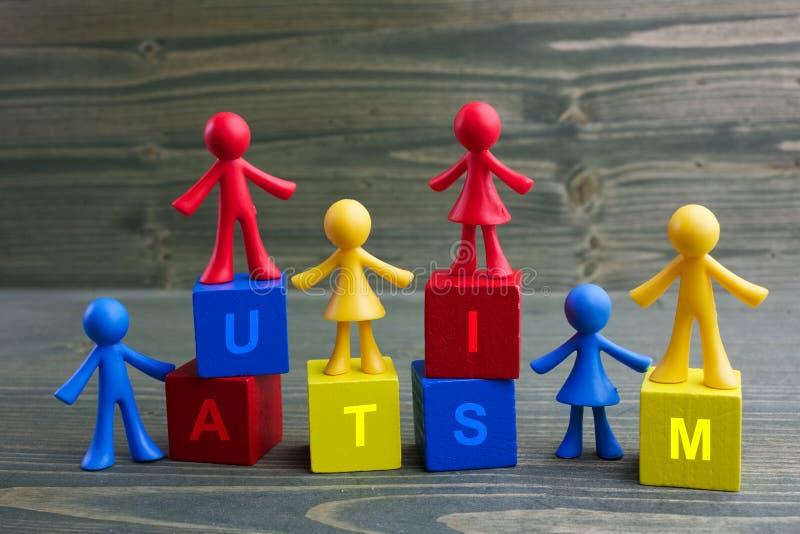 Puppenkinder entwerfen mit Autismuswort auf hölzernem Hintergrund lizenzfreie stockbilder
