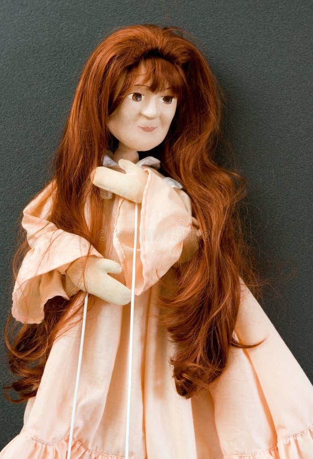 Puppet Actress. Rod puppet- long hair orange-pink cloth royalty free stock image