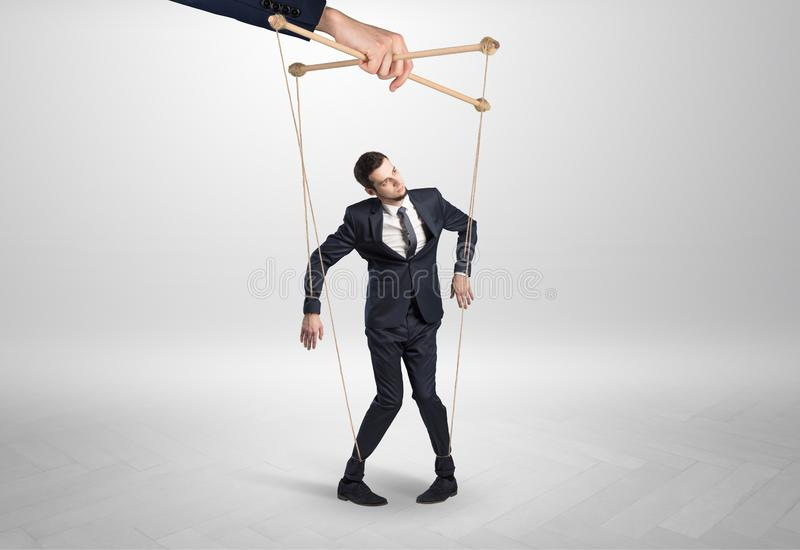 Puppet businessman leaded by a huge hand royalty free stock images