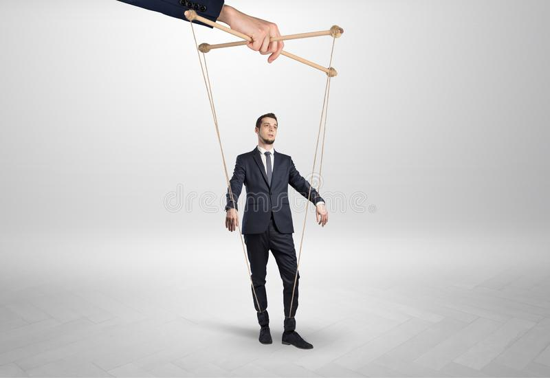 Puppet businessman leaded by a huge hand royalty free stock photos