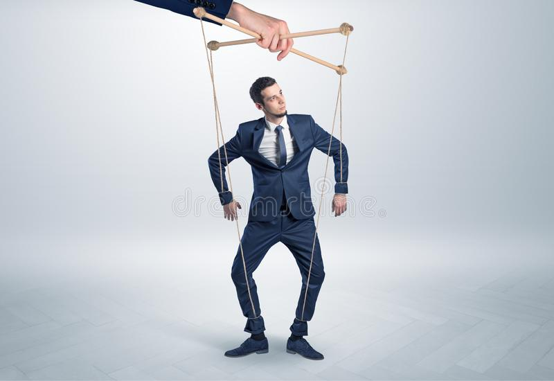 Puppet businessman leaded by a huge hand stock photo